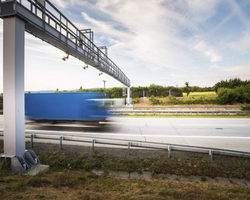 truck passing through a toll gate on a highway (motion blurred i